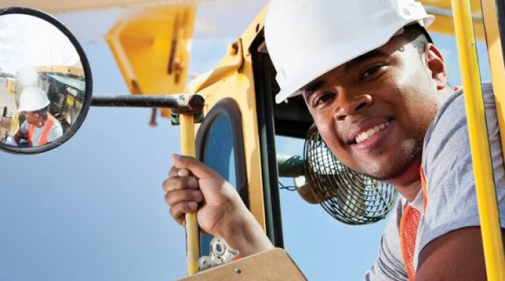 African American man, 20s, on crane at manufacturing facility.