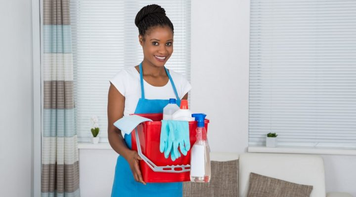 50691540 - smiling african woman holding basket with cleaning equipment